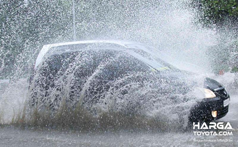 Gambar ini menunjukkan sebuah mobil melewati genangan air