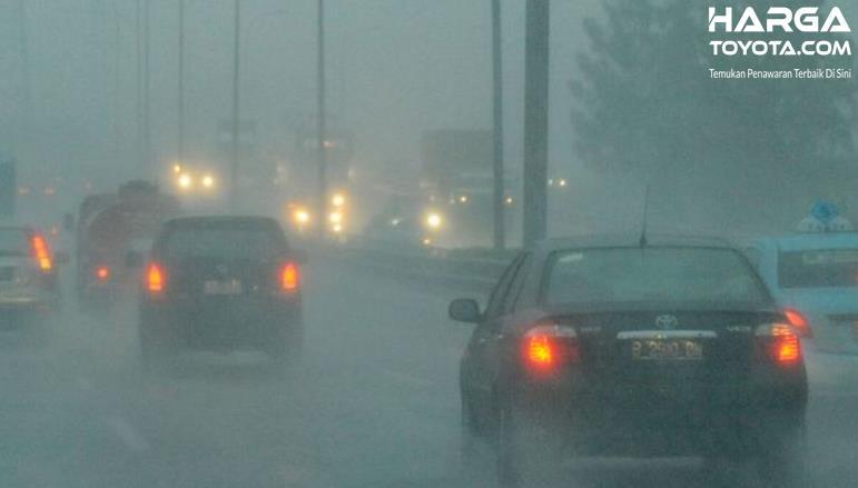 Gambar ini menunjukkan beberapa mobil melaju di jalan dalam kondisi hujan deras