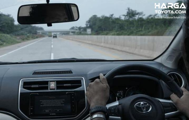 Gambar ini menunjukkan seseorang sedang mengemudi mobil Toyota