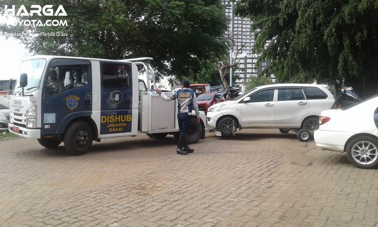 Foto menunjukkan Toyota Avanza diderek petugas DisHub karena parkir sembarangan