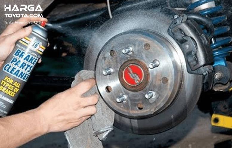 Gambar ini menunjukkan proses penyemprotan rem cakram mobil