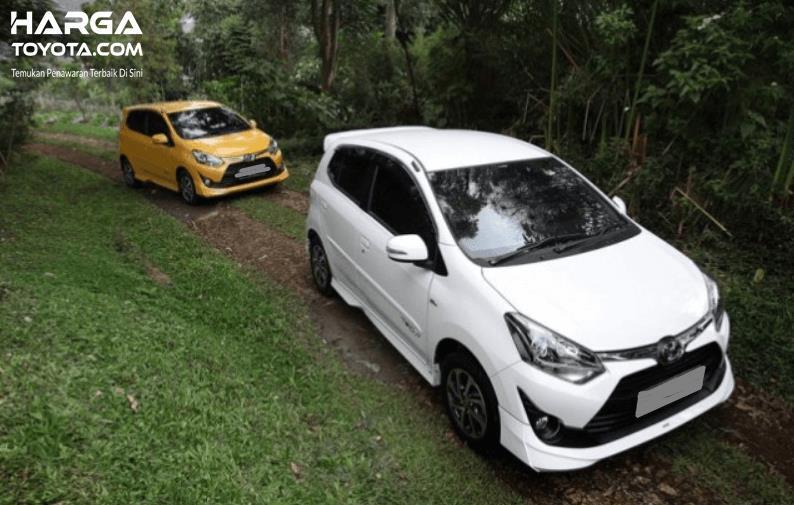 Gambar ini menunjukkan 2 mobil Toyota Agya warna putih dan kuning