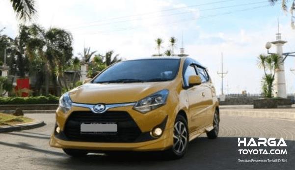 Gambar ini menunjukkan mobil Toyota Agya warna kuning tampak depan