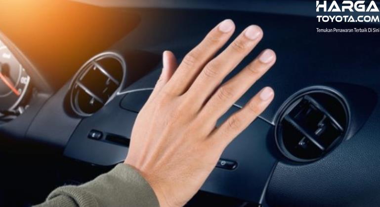 Gambar ini menunjukkan tangan berada pada kisi-kisi AC mobil