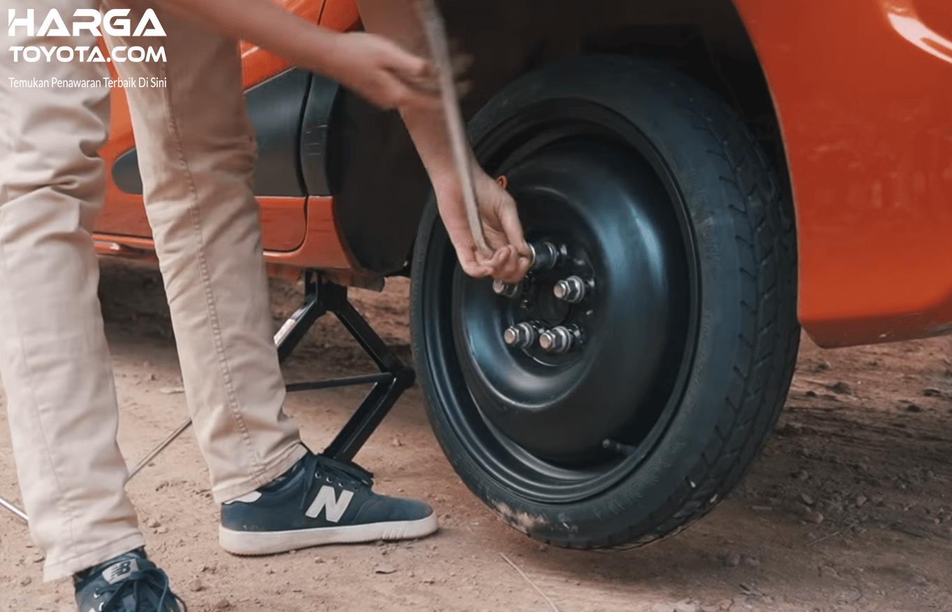 Gambar ini menunjukkan seseorang sedang mengencangkan ban serep pada mobil