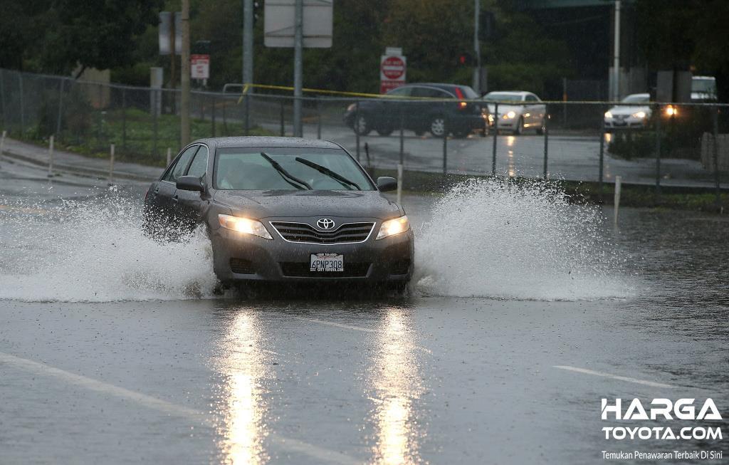 Foto mobil Toyota berjalan melintasi genangan air