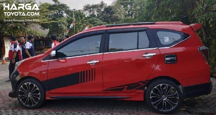 Gambar ini menunjukkan mobil Toyota Calya merah tampak samping