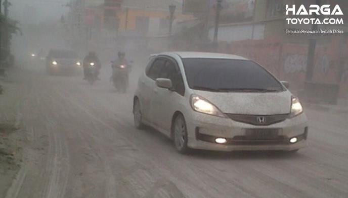 Gambar ini menunjukkan mobil Honda putih melaju ndi jalan yang terdapat abu vulkanik