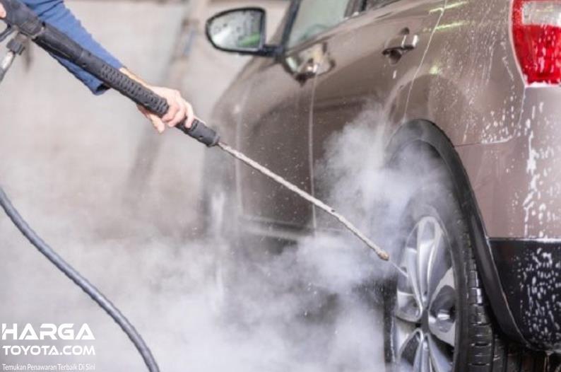 Gambar ini menunjukkan mobil sedang disemprot dengan air bertekanan