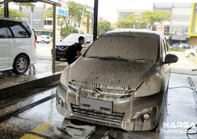Gambar ini menunjukkan mobil terkena abu vulkanik akan dicuci