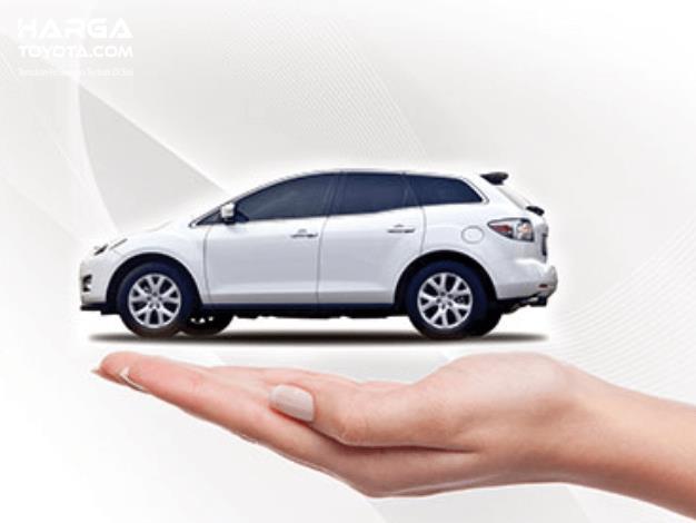 Gambar ini menunjukkan ilustrasi sebuah nmobil putih di atas tangan