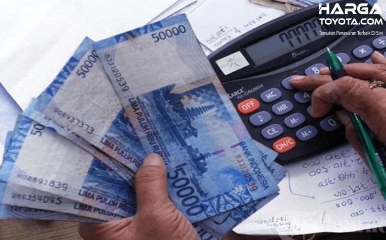 Gambar ini menunjukkan uang 50 ribuan dan kalkulator serta tangan memegang bolpen