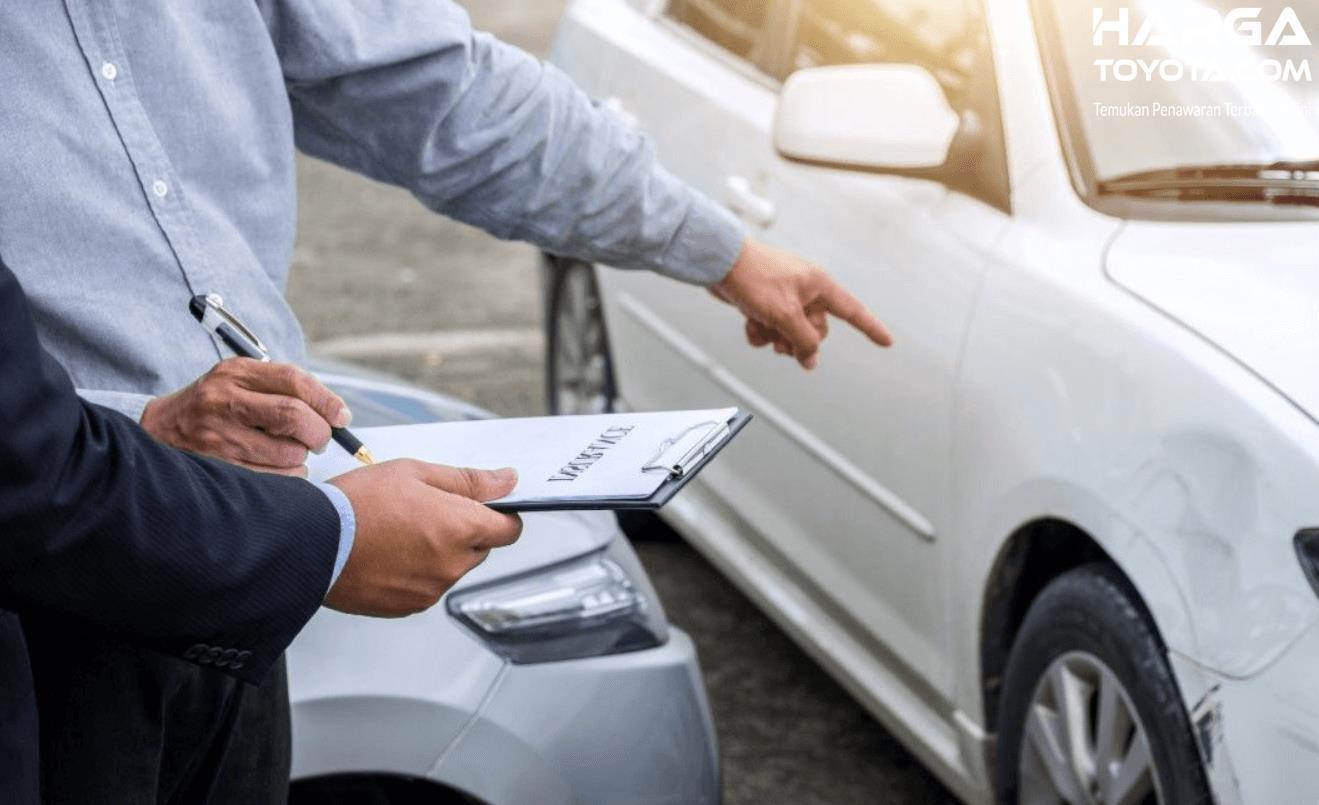 Gambar ini menunjukkan 2 orang sedang melihat kerusakan pada mobil
