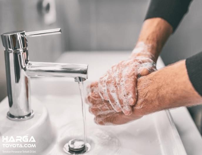 Gambar ini menunjukkan 2 buah tangan sedang dicuci dengan air dan sabun