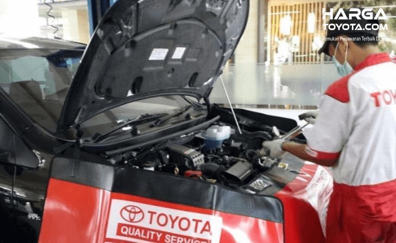 Gambar ini menunjukkan seorang melanik Toyota memeriksa mesin  mobil