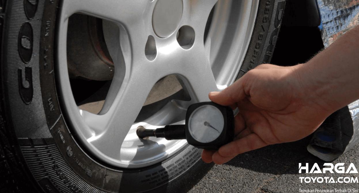 Gambar ini menunjukkan pengecekan tekanan angin ban mobil