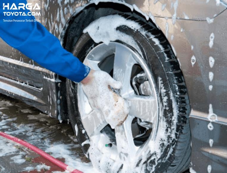 Gambar ini menunjukkan sebuah tangan membersihkan pelek mobil