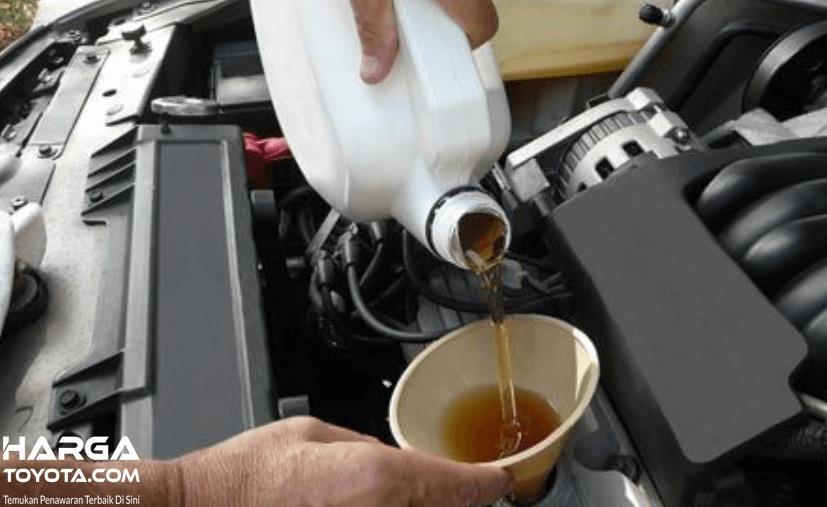 Gambar ini menunjukkan sebuah tangan membawa derijen  mengisi mesin mobil