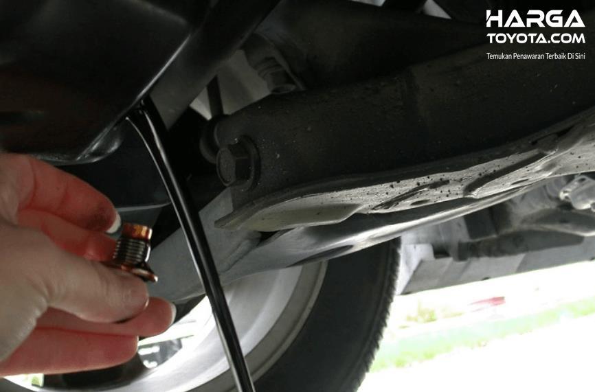 Gambar ini menunjukkan sebuah tangan membuka tutup pembuangan oli