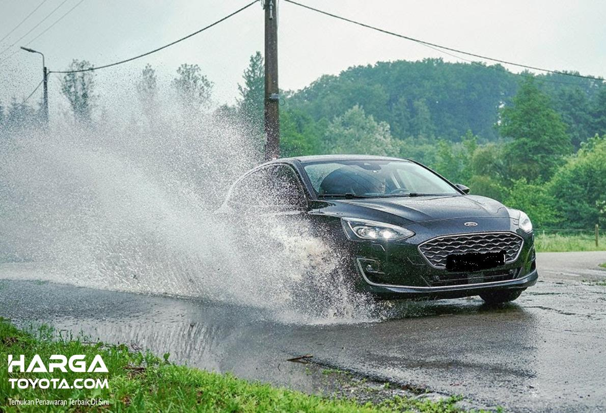 Gambar ini menunjukkan mobil melaju melewati genangan air di jalan