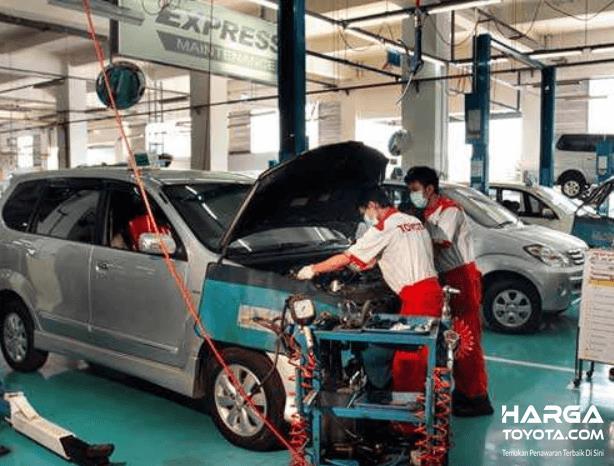Gambar ini menunjukkan mekanik sedang memperbaiki mobil