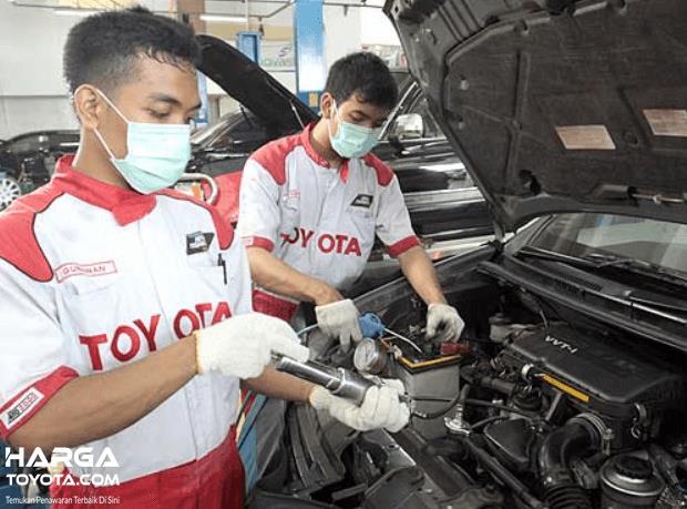 Gambar ini menunjukkan 2 mekanik sedang memperbaiki mesin mobil