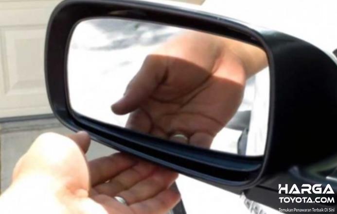 Gambar ini menunjukkan sebuah tangan memegang kaca spion mobil