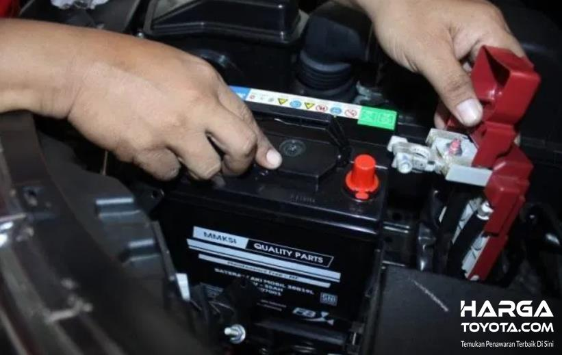 Gambar ini menunjukkan 2 buah tangan memegang aki mobil