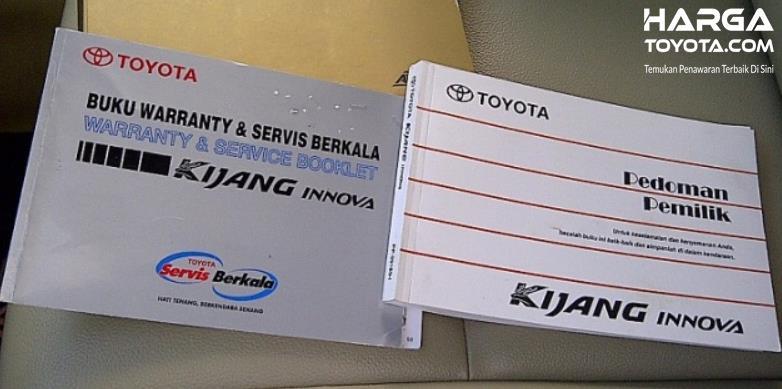 Gambar ini menunjukkan buku manual kendaraan dan buku servis