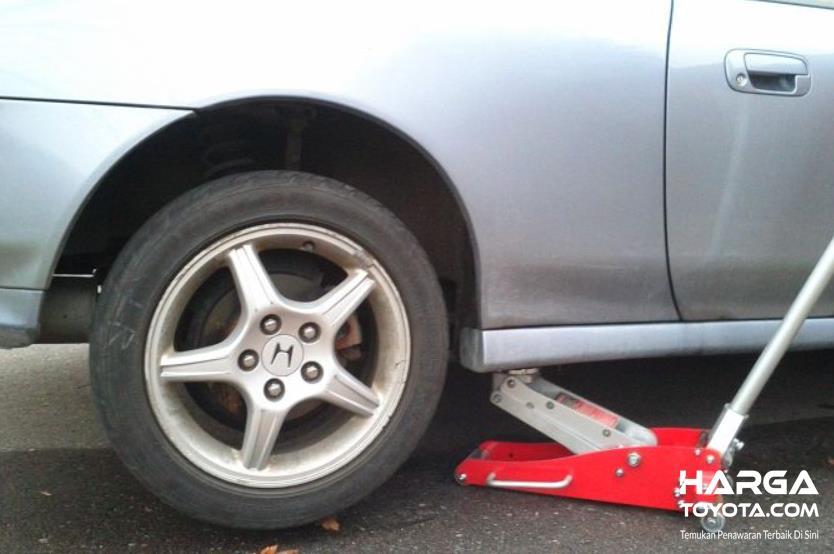 Gambar ini menunjukkan sebuah mobil sedang didongkrak