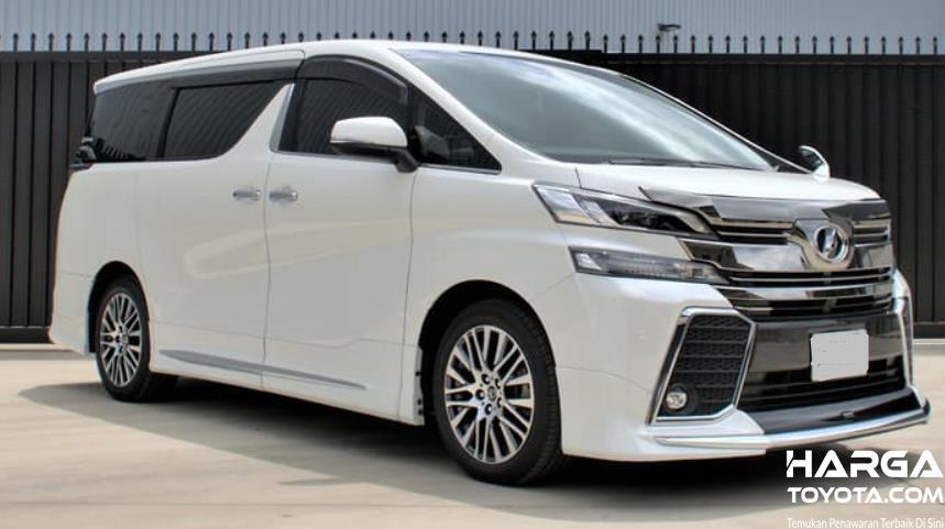 Gambar ini menunjukkan mobil Toyota Vellfire warna putih tampak depan dan samping kanan