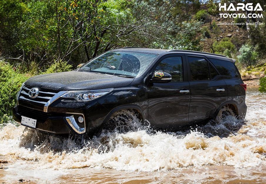 Gambar ini menunjukkan mobil Toyota Fortuner melewati sungai