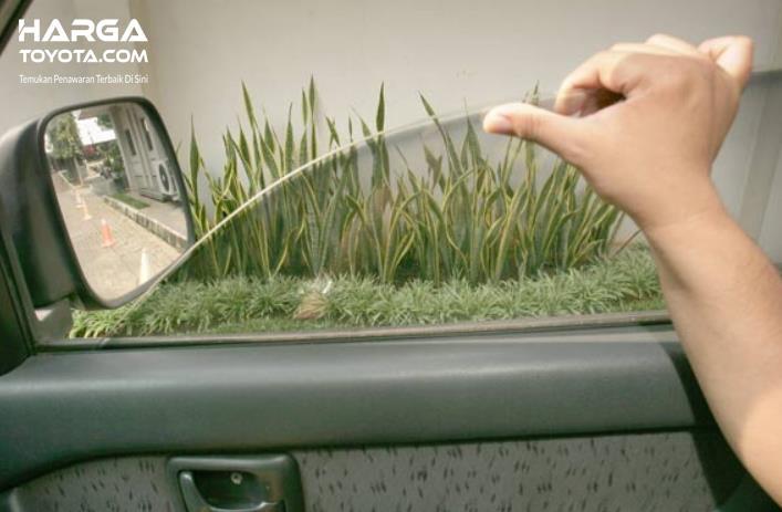 Gambar ini menunjukkan sebuah tangan memegang kaca jendela mobil