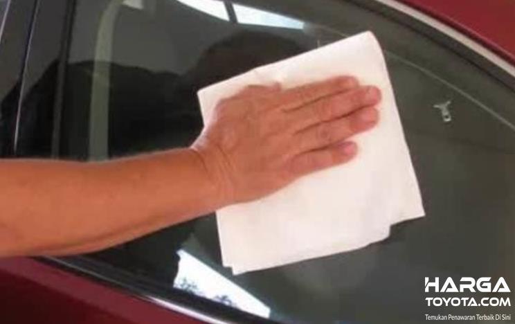 Gambar ini menunjukkan sebuah tangan memegang kain mengelap kaca mobil