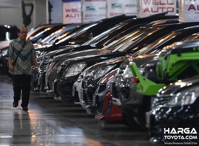Gambar ini menunjukkan beberapa mobil bekas dan 1 orang berjalan di depannya