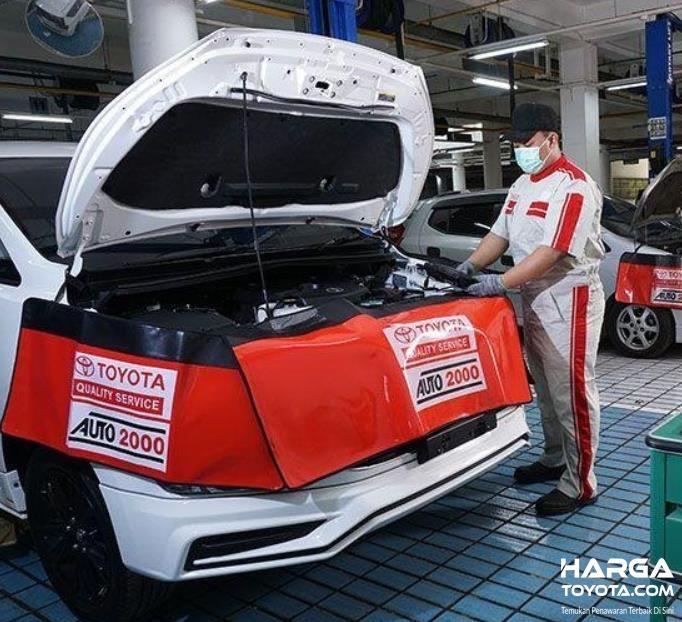 Gambar ini menunjukkan mekanik Toyota sedang memperbaiki mesin mobil Toyota