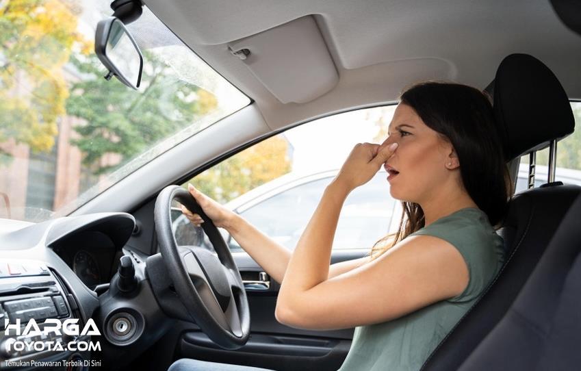 Gambar ini menunjukkan seorang wanita menutup hidungnya di mobil