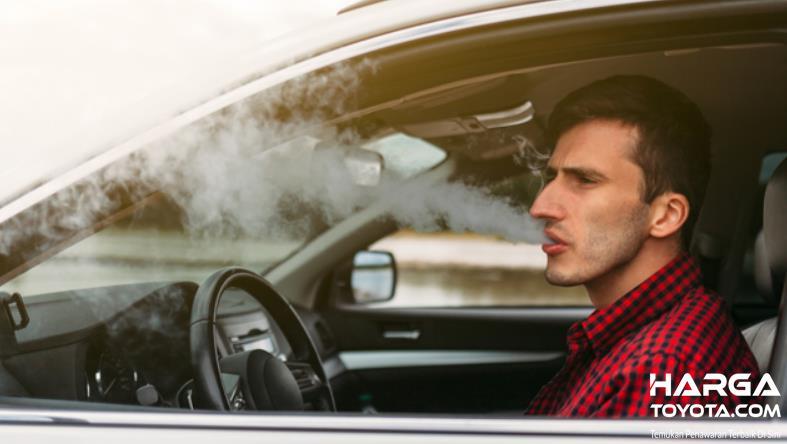 Gambar ini menunjukkan pengemudi sedang merokok di mobil