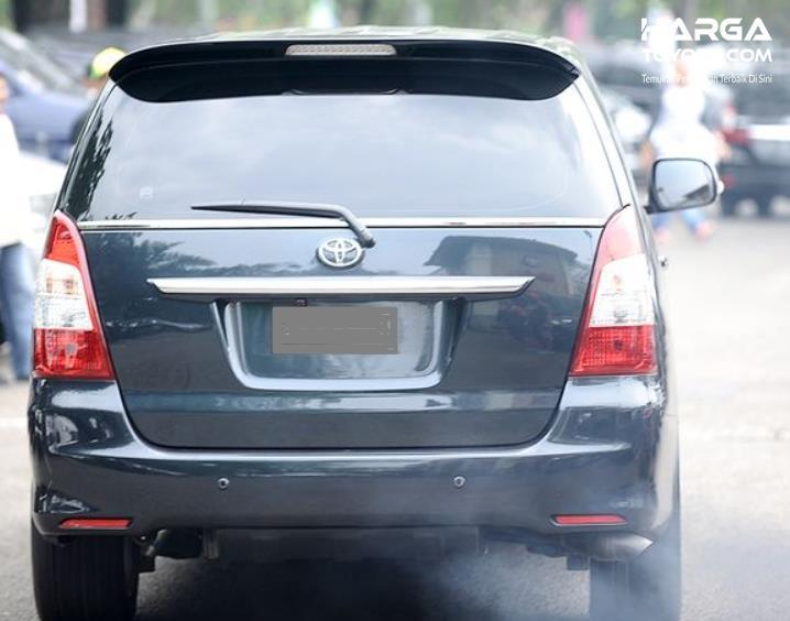 Gambar ini menunjukkan sebuah mobil tampak belakang dengan knalpot keluar asap putih