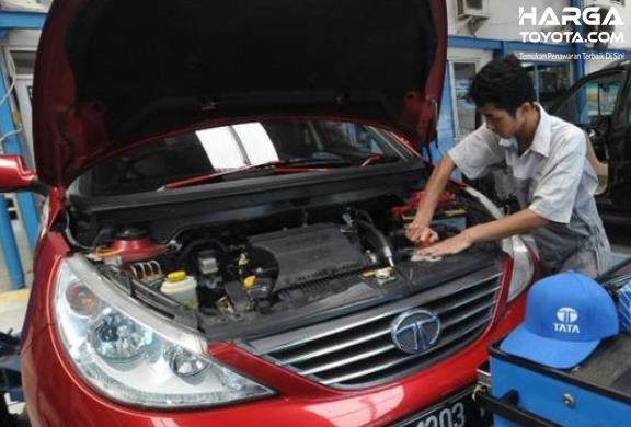 Gambar ini menunjukkan seorang mekanik melihat mesin mobil warna merah