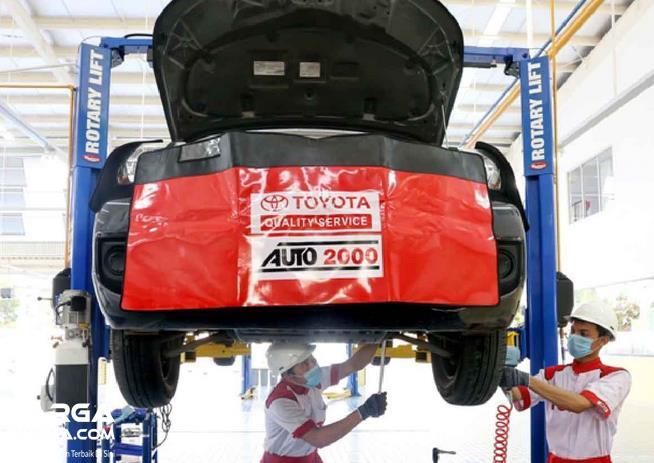Gambar ini menunjukkan 2 mekanik memeriksa sebuah mobil