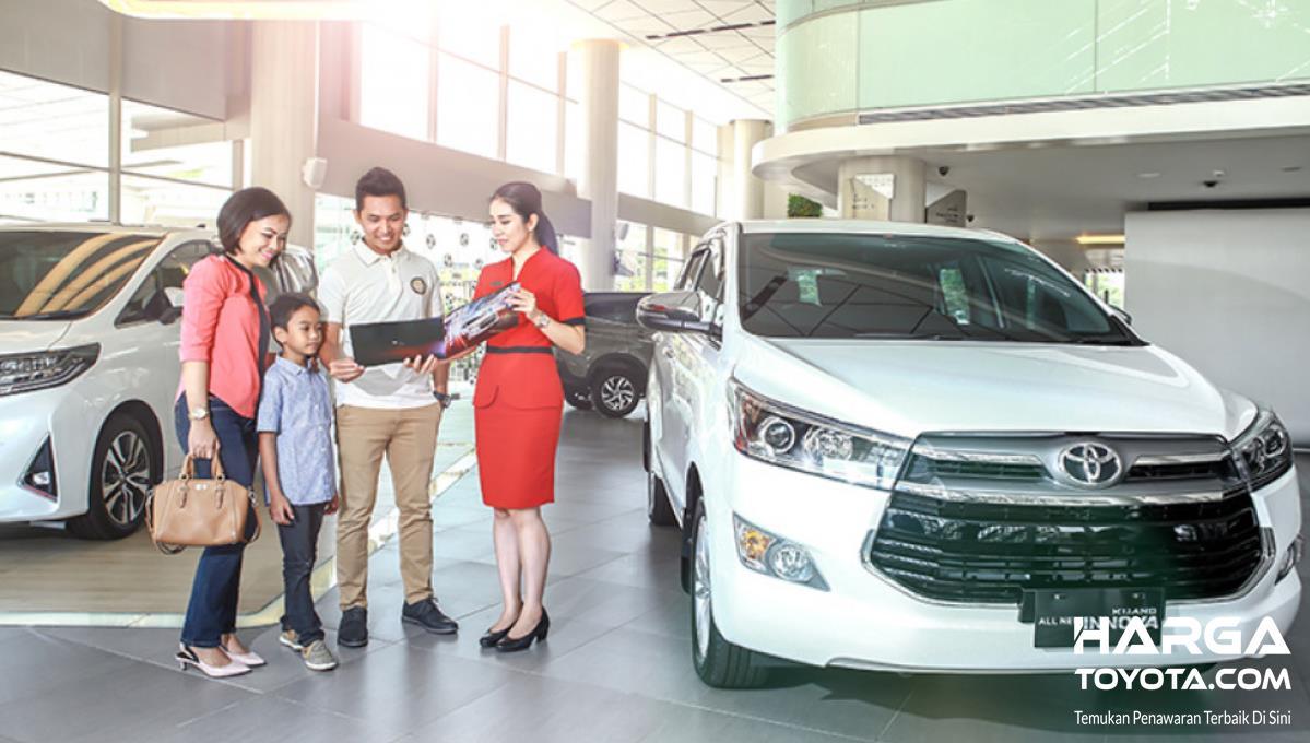 Gambar ini menunjukkan sekeluarga berdiri dekat sales dan mobil