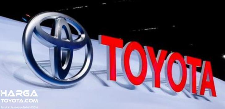 Gambar ini menunjukkan logo mobil Toyota dengan tulisan warna merah