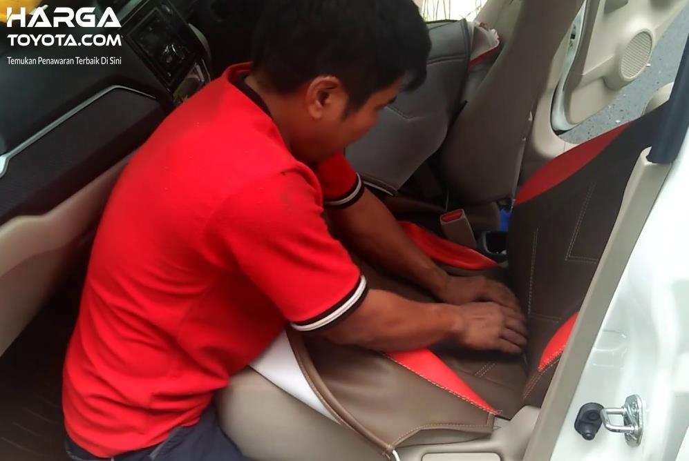 Gambar ini menunjukkan pemasangan cover jok mobil