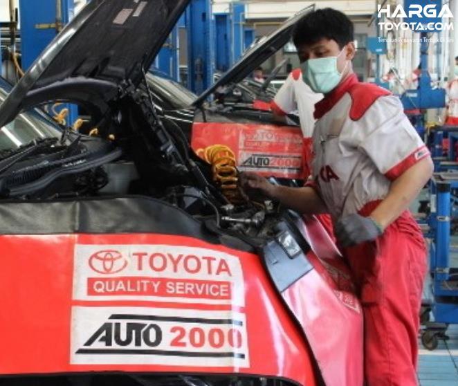 Gambar ini menunjukkan seorang mekanik sedang memperbaiki mesin mobil