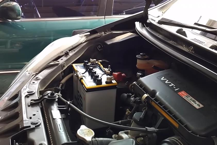 Gambar ini menunjukkan mesin dan aki mobil Toyota Avanza
