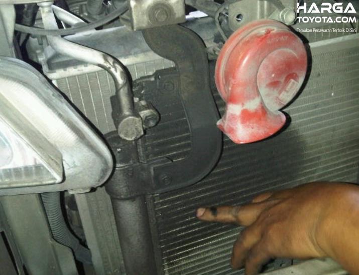 Gambar ini menunjukkan tangan menunjuk kondensor AC mobil