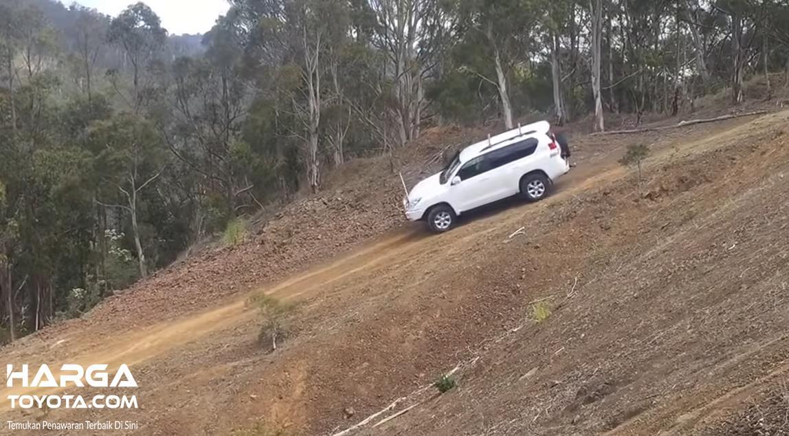 Gambar ini menunjukkan mobil Toyota putih melewati jalanan menurun