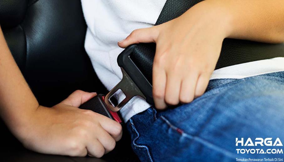 Gambar ini menunjukkan proses pemasangan seat belt mobil