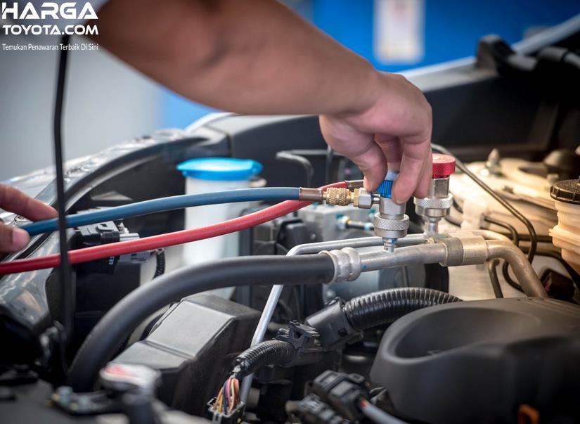 Gambar ini menunjukkan pengisian freon AC mobil